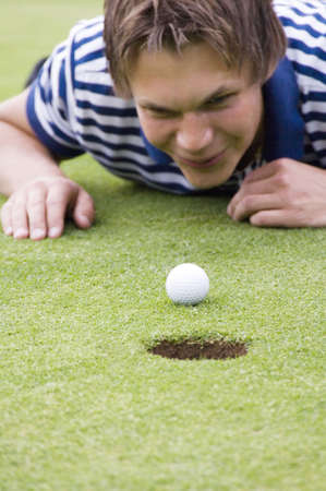 Man lying down looking at golf ball LANG_EVOIMAGES