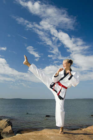 Woman giving a high kick LANG_EVOIMAGES