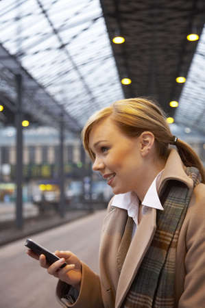 Woman text messaging while waiting for the train Stock Photo - 3194039
