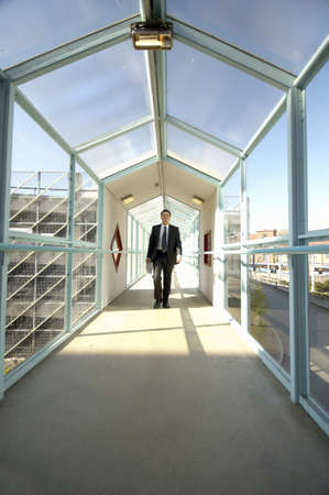 Businessman holding paperwork while walking