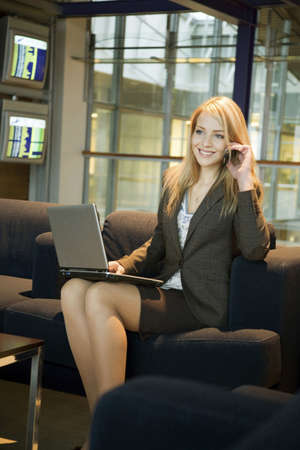 Businesswoman using laptop while talking on mobile