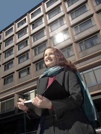 Businesswoman smiling while holding organizer Stock Photo - 3194046