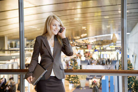Businesswoman holding laptop while talking on mobile at airport terminal Stock Photo - 3194048