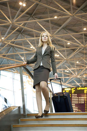 Businesswoman with luggage walking down the stairs at the airport terminal Stock Photo - 3194050