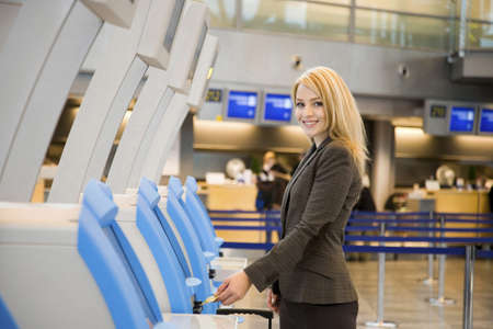 Businesswoman using an automated check-in machine Stock Photo - 3194052