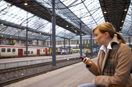 Woman text messaging while waiting for the train