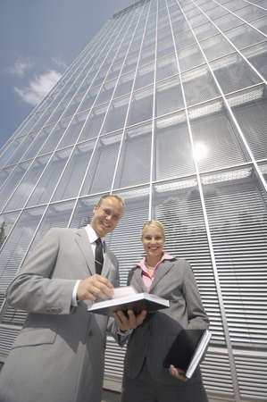 Businessman and businesswoman smiling at the camera Stock Photo - 3194057