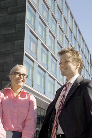 Businessman and businesswoman smiling LANG_EVOIMAGES