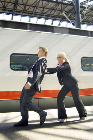 Businesswoman pushing businessman from the back forcing him to walk