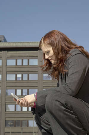 Businesswoman squatting down text messaging on the mobile phone Stock Photo - 3194062