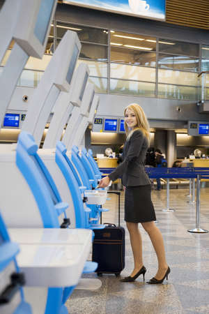 Businesswoman using an automated check-in machine
