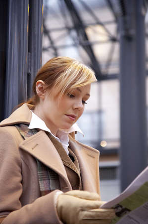 Woman reading newspaper while waiting for the train Stock Photo - 3194083