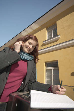 Businesswoman writing while talking on the phone