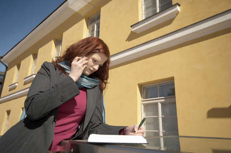 Businesswoman writing while talking on the mobile phone LANG_EVOIMAGES