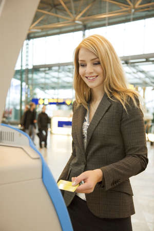 Businesswoman using an automated check-in machine Stock Photo - 3194095