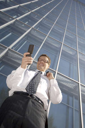 Businessman smiling while text messaging on the mobile phone Stock Photo - 3194096
