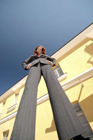 Businesswoman standing with arms akimbo looking down at the camera LANG_EVOIMAGES