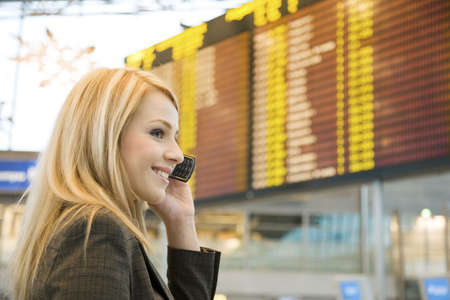 mobile communication: Woman talking on the mobile with arrival departure board in the background