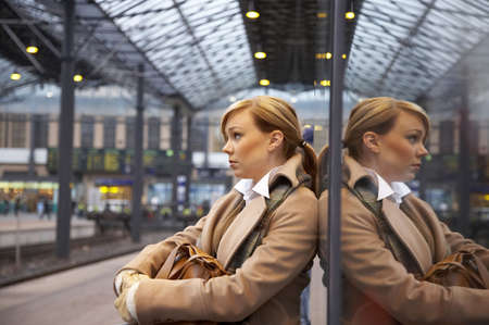 woman mirror: Woman waiting for the train at the railway station LANG_EVOIMAGES