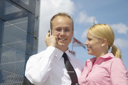 Businesswoman looking at businessman talking on the mobile phone LANG_EVOIMAGES