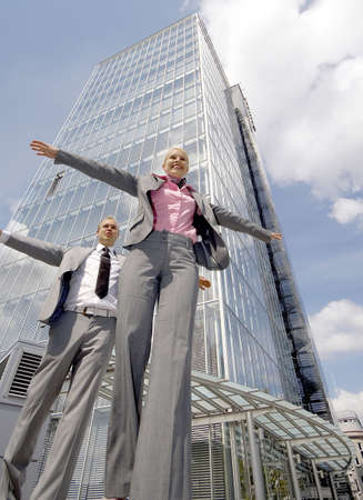 Businessman and businesswoman balancing themselves while walking in a straight line