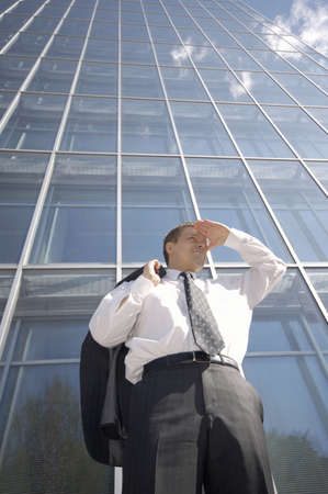 Businessman shielding his eyes while looking into the distance Stock Photo - 3194111