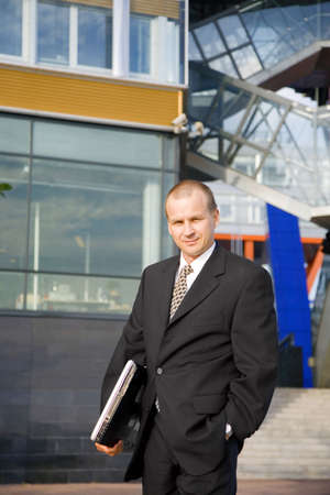 Businessman posing with laptop outdoors