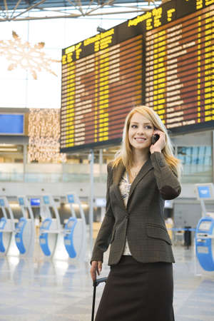 Woman talking on the mobile with arrival departure board in the background Stock Photo - 3194121