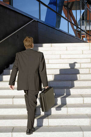 shadow: Businessman walking up the stairs of a building