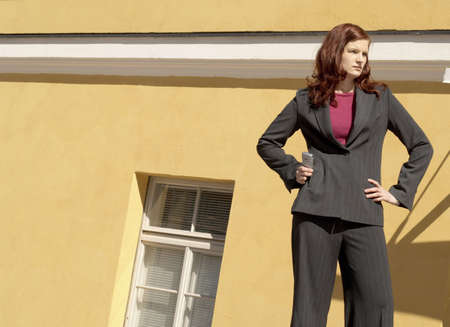 Businesswoman standing with arms akimbo holding mobile phone