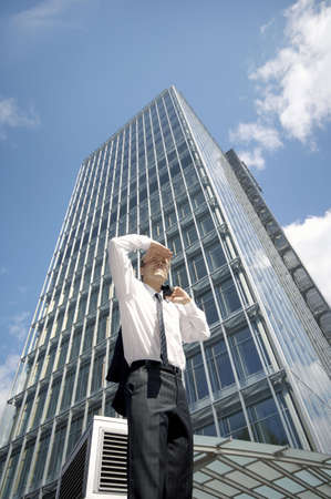 Businessman shielding his eyes while looking into the distance