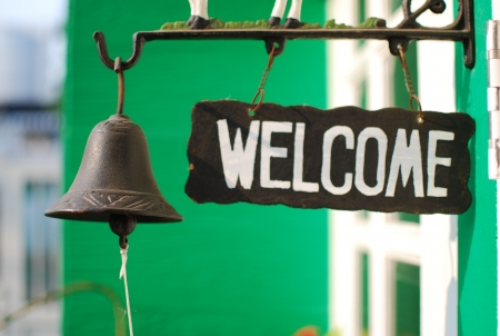Green welcome tag with old bell