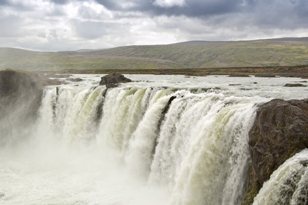 deafening: Godafoss waterfall (Iceland). The Godafoss is one of the most spectacular waterfalls in Iceland. The water of the river Skjalfandafljot falls from a height of 12 meters over a width of 30 meters.