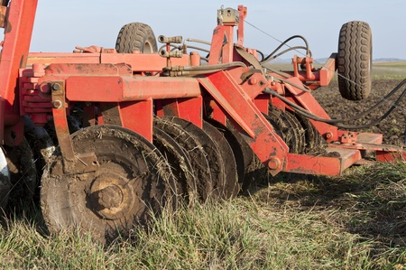 implements: Disk Ripper in the field  Plough is a tool used in farming for initial cultivation of soil