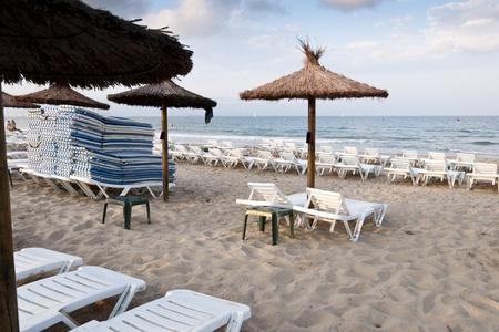 Sun loungers at Mediterranean beach, Alicante, Spain photo