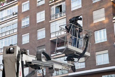 elevator operator: Cameraman working on an aerial work platform Stock Photo