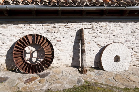 gristmill: Waterwheel, wooden axle and millstone of an old restored water mill  Picture taken in La Hiruela, Madrid, Spain