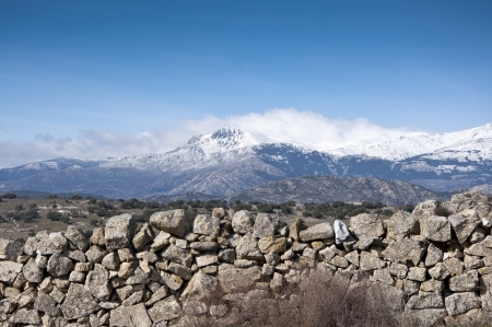 viejo: Stone wall  At the background, snow capped peaks of the Guadarrama Mountains  Photo taken in Colmenar Viejo, Madrid Province, Spain