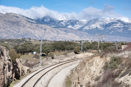 Rail road  At the background, snow capped peaks of the Guadarrama Mountains  Photo taken in Colmenar Viejo, Madrid Province, Spain  Stock Photo
