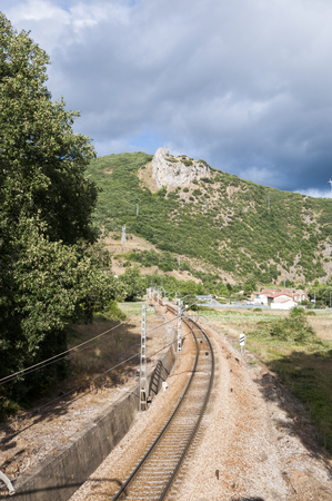 forest railroad: Iberian gauge railway track between Leon and Gijon on its way through La Pola de Gordon, Leon Province, Spain. In the background can be seen the town of Puente de Alba Stock Photo
