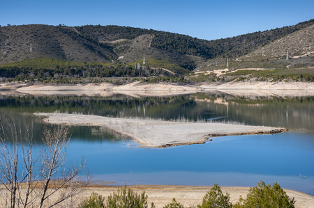 Views of Buendia Reservoir, in the upper waters of the river Tagus, Cuenca, Castilla La Mancha, Spain. The surface area of the reservoir measures 8,194 hectares, and it can hold a total of 1,638 cubic hectometres. Stock Photo
