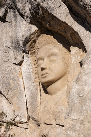 ruta: Sculptures carved on sandstones in the Ruta de las Caras, Route of the Faces, a hiking route at the shore of Buendia Reservoir, Cuenca, Spain.