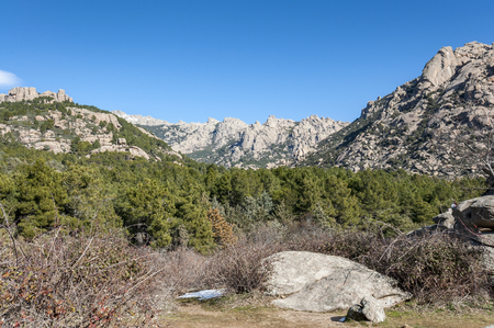 canto: Views of La Pedriza from Canto Cochino, in Guadarrama Mountains National Park, Madrid, Spain. In the background can be seen The Cancho de los Muertos (Peak of the deads), El Pajaro (Bird Peak), Las Buitreras (Vulture Peak) and Sirio Peak