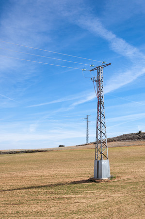 the arable land: Electricity pylon in an agricultural landscape in Toledo Province, Spain Stock Photo