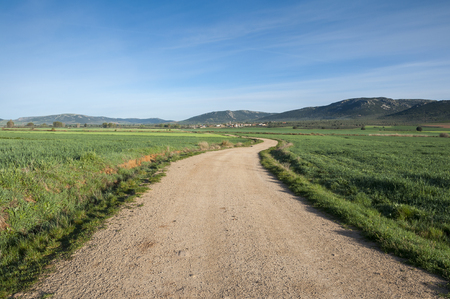 the arable land: Small hamlet in an agricultural landscape in La Mancha, Ciudad Real Province, Spain. In the background can be seen the Toledo Mountains