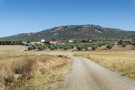 agrarian: Small hamlet in an agricultural landscape in La Mancha, Ciudad Real Province, Spain. In the background can be seen the Toledo Mountains