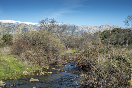 Views of the Fuentiduena stream on its way through the city of Cerceda, in the province of Madrid, Spain. In the background it can be seen The Guadarrama Mountains