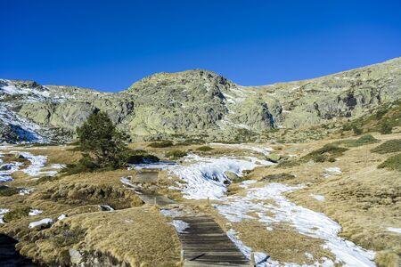 Wooden walkway to de Penalara Lagoon, in the municipality of Rascafria, Guadarrama Mountains National Park, province of Madrid, Spain Stock Photo