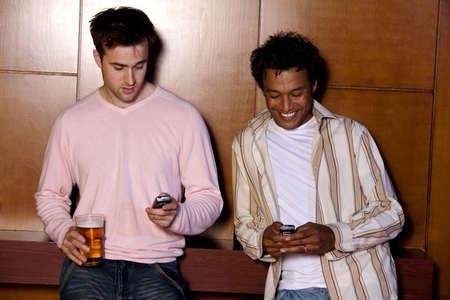 Dos hombres de mensajes de texto en sus tel�fonos