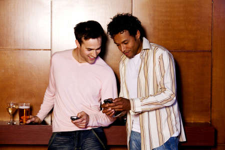 Two men text messaging on their phones